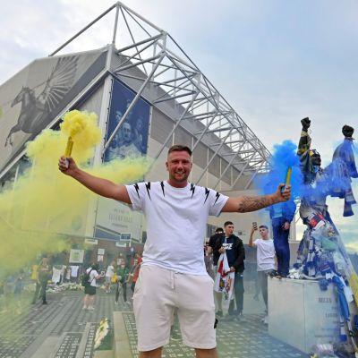 En supporter firar Leeds Uniteds avancemang utanför arenan Elland Road.