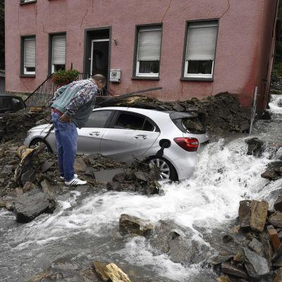 En person granskar hur huset skadats av vattnet.