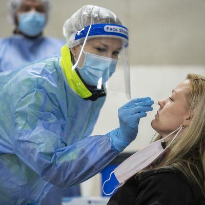 lähihoitaja Jenny Järvi ottamassa näytettä Terhi Lammiselta.