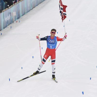 Kläbo med den norska flaggan i handen då han korsar mållinjen