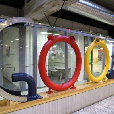 Ett konstverk där färgglada rördelar har böjts och arrangerats så atyt de bildar ordet Google