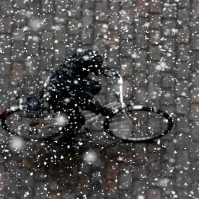 Cyklist fotograferad ovanifrån i snöstorm.