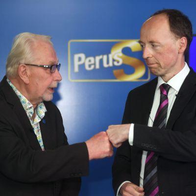 """Matti Putkonen och Jussi Halla-aho gör en så kallad """"fistbump"""" framför en blå Sannfinländar-plansch."""
