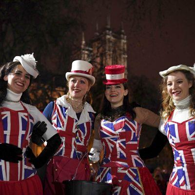 Tre damer klädda i blårödvita union jack-klänningar och hattar.