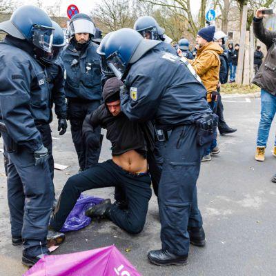 En demonstrant förs bort av kravallpolis under demonstrationen mot Alternativ för Tyskland i Hannover 2.12.2017.
