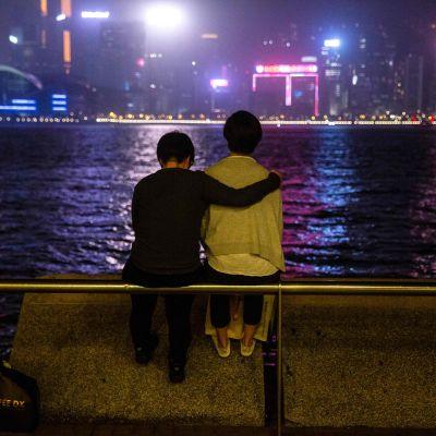 Ett par tittar ut över hamnen i Victoria Harbour i Hongkong 21.3.2020