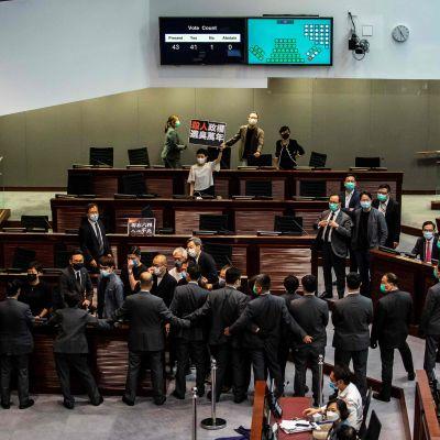 Protesterande prodemokratiska parlamentsledamöter i Hongkongs parlament under debatten om nationalsångslagen 4.6.2020 d