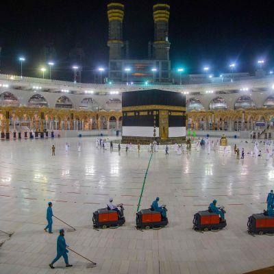 Hygieniatyöntekijät siivoavat Masjid al-Haramin moskeijaa samanaikaisesti, kun muslimipyhiinvaeltajat rukoilevat Kaaban pyhän rakennuksen edessä.