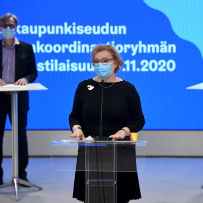 Tre personer står håller pressträff. Två män i bakgrunden, en kvinna längst fram i bilden.