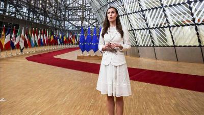 Sanna Marin i vit klädsel, hon träffar media inför ett EU-toppmöte i Bryssel