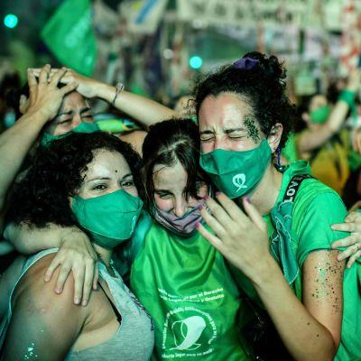Människor klädda i gröna kläder firar utanför senaten i Argentina efter att abort legaliserats i landet.