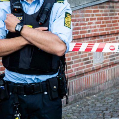 Polis står med korsade armar framför ett avspärrningsband.