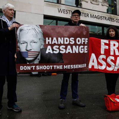 """Demonstration för Julian Assange i London 19.2.2020. Plakat där det står Släpp Assange"""", """"Rör inte Assange"""", """"Skjut inte budbäraren"""""""