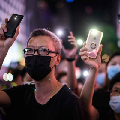 Demonstranter i Hongkong håller upp sina mobiler med mobilernas ficklampor tända.