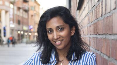 Porträttbild av en mörkhårig kvinna iklädd blårandig skjorta. Hon lutar mot en tegelvägg, ler och tittar in i kameran.
