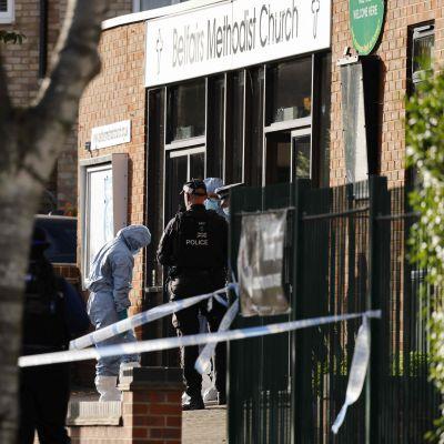 Poliser och polisens tekniker står vid dörren till kyrkan där Sir David Amess knivhöggs.