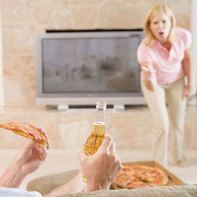 Kvinna i bakgrunden skriker åt man som äter pizza och dricker öl