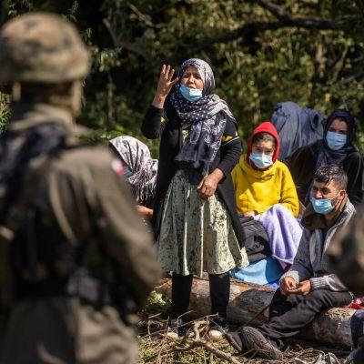 Afganistanilaisia pakolaisia Puolan ja Valko-Venäjän rajalla 20. syyskuuta. Sotilaat estävät heidän kulkuaan.
