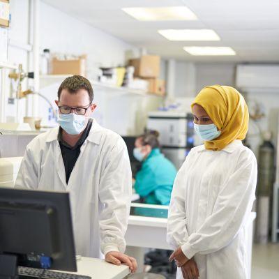Nainen ja mies katsovat tietokonetta laboratoriossa kasvomaskit päällään.