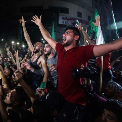 Hundratals män lyfter händerna i vädret och firar. En del gör segertecknet.