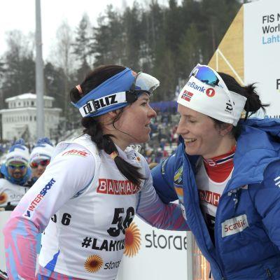 Marit Björgen iklädd blå dunjacka kramar om Krista Pärmäkoski.