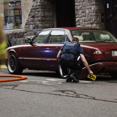En polis utför en teknisk undersökning av en bil på platsen där en kvinna omkom och flera skadades då en person vansinneskörde i Helsingfors på fredagskvällen den 28 juli 2017.