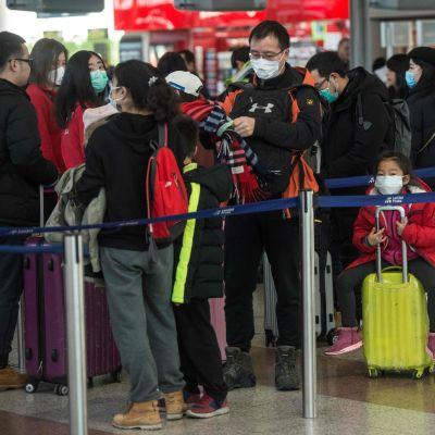 På bilden syns resenärer som köar till flyg på väg till Shangai på en flygplats i Prag.
