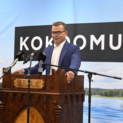 Petteri Orpo står och håller tal vid partimötet i Seinäjoki, bakom sig har han ett sjölandskap.