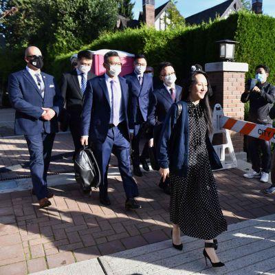 Kvinna i klänning går utomhus i soligt väder med en grupp kostymklädda män i munskydd. Huaweis finanschef Meng Wanzhou lämnar sitt hem i Vancouver den 24 september 2021.