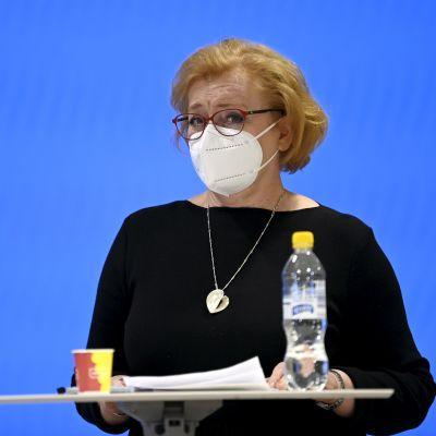 Ritva Viljanen i vitt munskydd och svart klänning mot blå bakgrund.