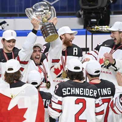 Kanadas lag samlat när en av spelarna lyfter VM-bucklan mot taket.