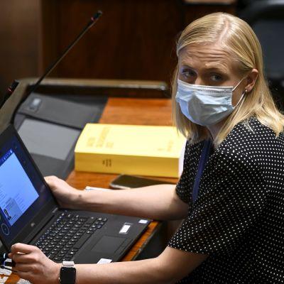 Riksdagsledamoten Elina Valtonen i munskydd sitter i riksdagen med en bärbar dator på bordet hon sitter vid.