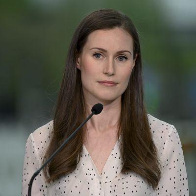 Sanna Marin i vitprickig skjorta.