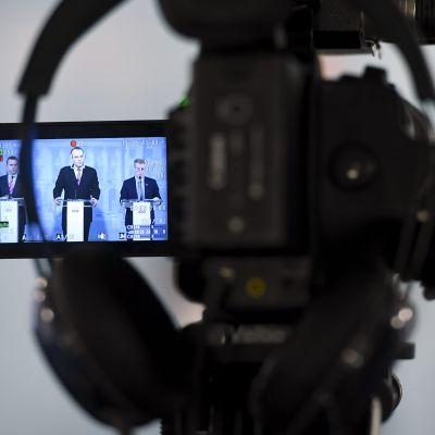 En kamera filmar försvarsminister Jussi Niinistö som håller presskonferens.
