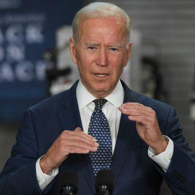 Joe Biden i blå kostym gestikulerar med händerna.