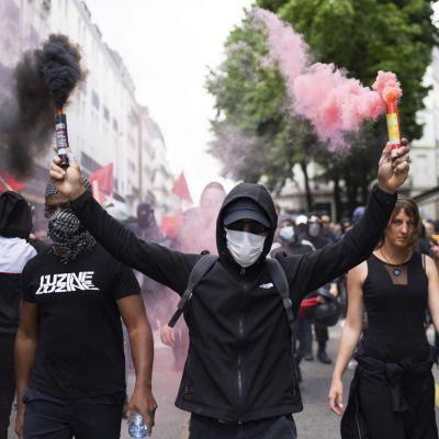 En demonstrant håller i två handbloss i en demonstrationståg.