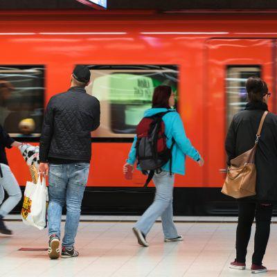Ihmisiä astumassa metrojunaan, metro Helsingin Rautatieasema
