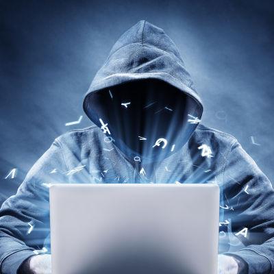 En person med huva över huvudet sitter vid en bärbar dator.