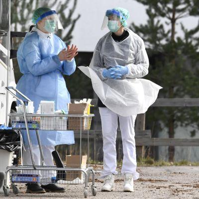 Två personer i ansiktsmasker och medicinska skyddskläder står utanför en bil.