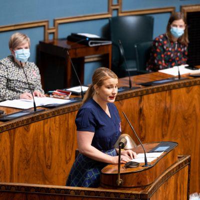 Vihreiden kansanedustaja Iiris Suomela eduskunnan istuntosalin puhujakorokkeella.