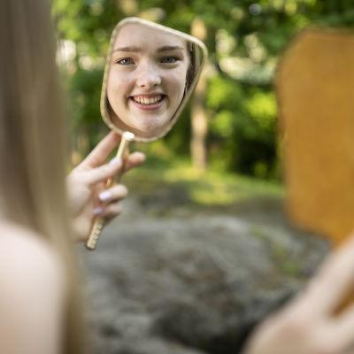 Tyttö katsoo peilistä kuvaansa ulkona.