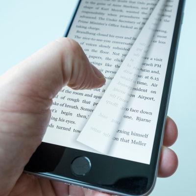 En tumme trycker på en mobiltelefon som har en text på sig och just nu byts sidan.