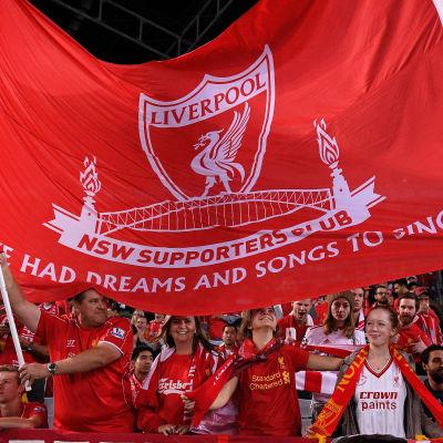 Liverpool FC:s fans håller upp stor rödvit flagga.
