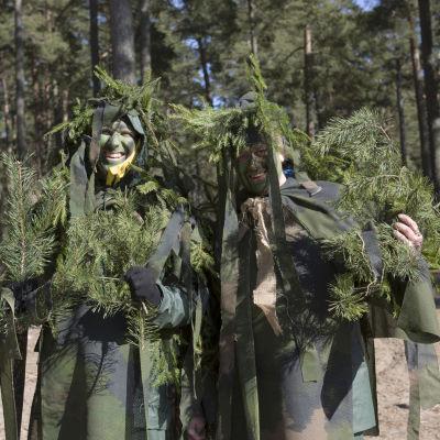 Köpi ja Viki naamioituneena havuihin ja vihreisiin vaatteisiin