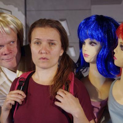 En kvinna ser in i kameran med ledsen blick. Två dockor och en manlig skådis i peruk omringar henne.