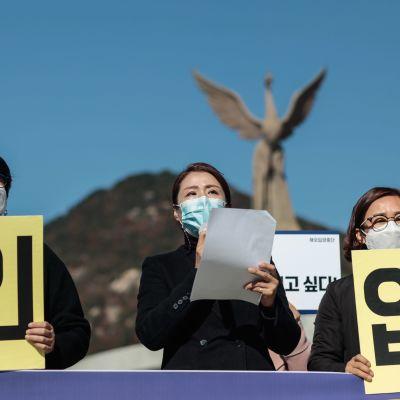 Tre kvinnor med munskydd håller upp plakat med koranska tecken. I bakgrunden en staty av Fågel Fenix.