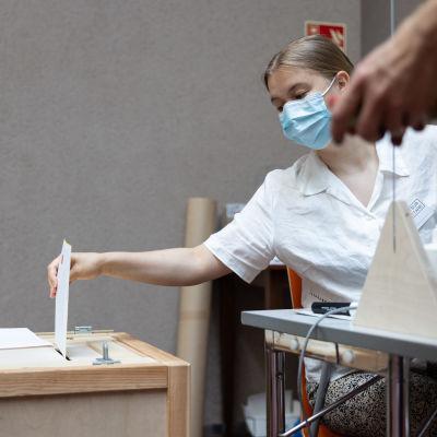 Vaalityöntekijä laittaa äänen kirjekuoressa vaaliuurnaan.