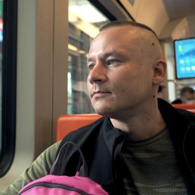 En man med snaggat hår ser ut genom metrovagnens fönster i Helsingfors.