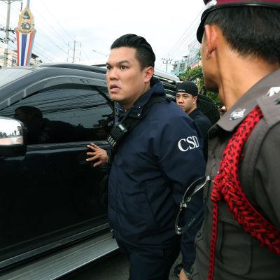 Den gripne tros vara inne i bilen som omges av thailändsk polis.