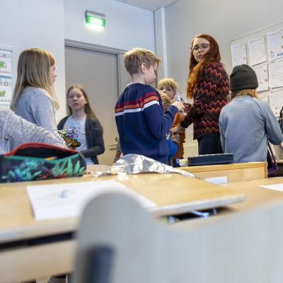 Kuvaamataidon opettaja jakaa ohjeita neljäsluokkalaisten oppilaiden ympäröimänä